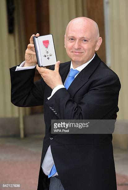 Tim Sigsworth poses after he received his Member of Order of the British Empire medal from the Princess Royal during an investiture ceremony at...