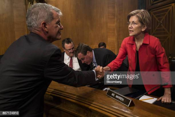 Tim Sloan chief executive officer and president of Wells Fargo Co shakes hands with Senator Elizabeth Warren a Democrat from Massachusetts right...