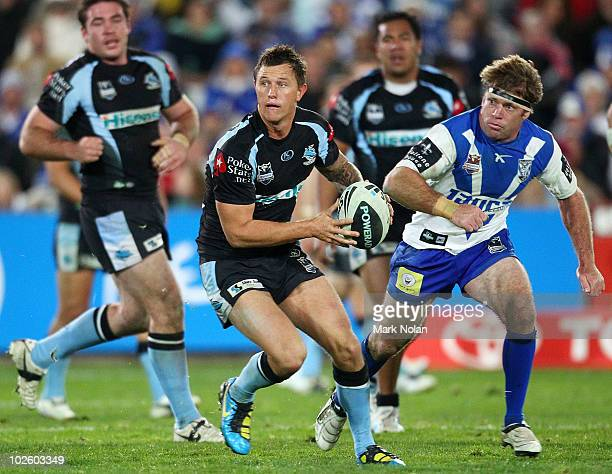 Tim Smith of the Sharks runs the ball as Brett Kimmorley of the Bulldogs defends during the round 17 NRL match between the Cronulla Sharks and the...