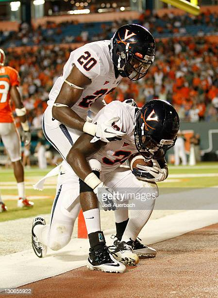 Tim Smith of the Virginia Cavaliers congratulates Perry Jones of the Virginia Cavaliers after he scored the final touchdown against the Miami...