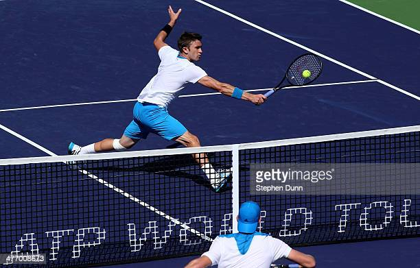 Tim Smyczek goes to the net to hit a return to Jack Sock during the BNP Paribas Open at Indian Wells Tennis Garden on March 6, 2014 in Indian Wells,...