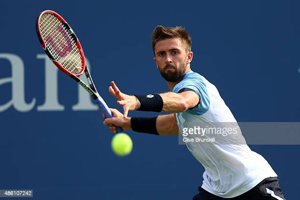 Tim Smyczek of the United States returns a shot against Milos Raonic of Canada during their Men's Singles First Round match on Day One of the 2015 US...
