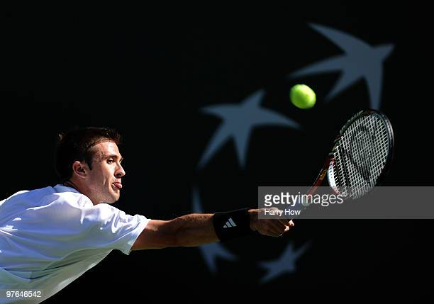 Tim Smyczek of the United States stretches for a backhand in his match against Carlos Moya of Spain during the BNP Paribas Open at the Indian Wells...