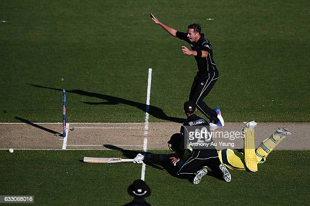Tim Southee of New Zealand celebrates as teammate Kane Williamson dismisses Josh Hazlewood of Australia on a run out to win the first One Day...