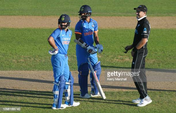 Tim Southee of New Zealand offers his sunglasses to Rohit Sharma of India as sun strike stops play during game one of the One Day International...
