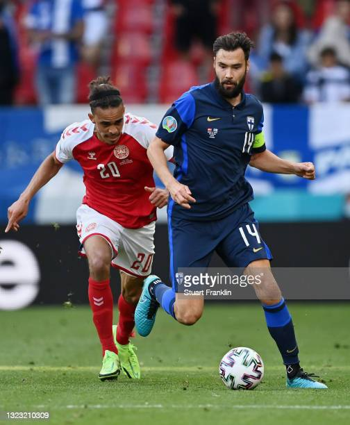 Tim Sparv of Finland runs with the ball whilst under pressure from Yussuf Poulsen of Denmark during the UEFA Euro 2020 Championship Group B match...