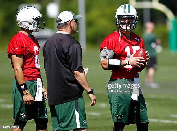 Tim Tebow and Mark Sanchez of the New York Jets listen to quarterbacks coach Matt Cavanaugh an organized team activity at the New York Jets practice...
