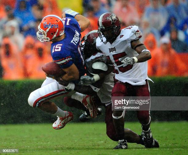 Tim Tebow of the Florida Gators is tackled by Barry Valcin and Cameron Sheffield of the Troy Trojans during the game at Ben Hill Griffin Stadium on...
