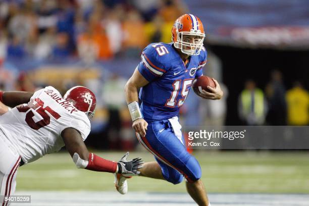 Tim Tebow of the Florida Gators runs the ball against Brandon Deaderick of the Alabama Crimson Tide before the SEC Championship on December 6 2008 at...
