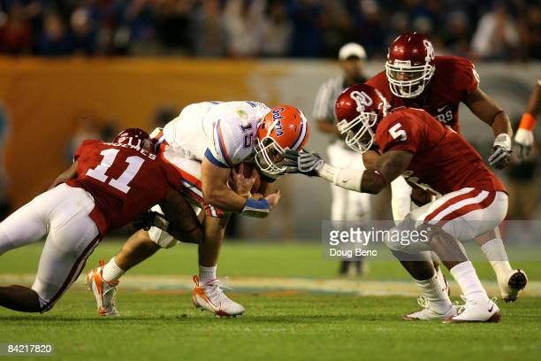 Tim Tebow of the Florida Gators runs the ball against Lendy Holmes of the Oklahoma Sooners during the FedEx BCS National Championship game at Dolphin...