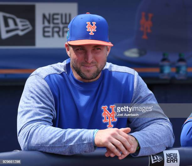 Tim Tebow of the New York Mets look on from the dugout prior to the spring training game against the New York Yankees at First Date Field on March 7...