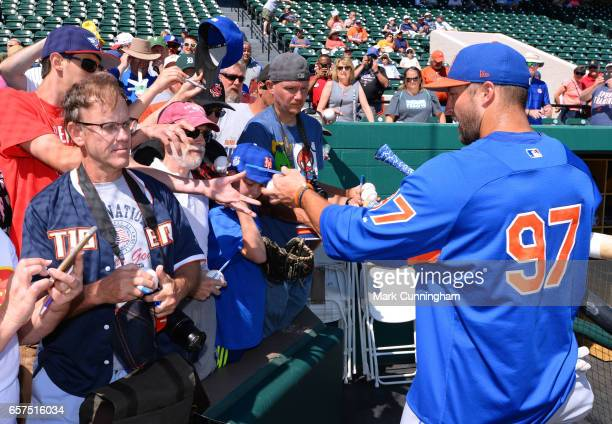 Tim Tebow of the New York Mets signs autographs for fans prior to the Spring Training game against the Detroit Tigers at Publix Field at Joker...