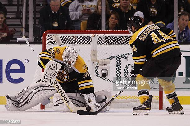Tim Thomas makes a save as Dennis Seidenberg of the Boston Bruins looks on against the Tampa Bay Lightning in Game Two of the Eastern Conference...