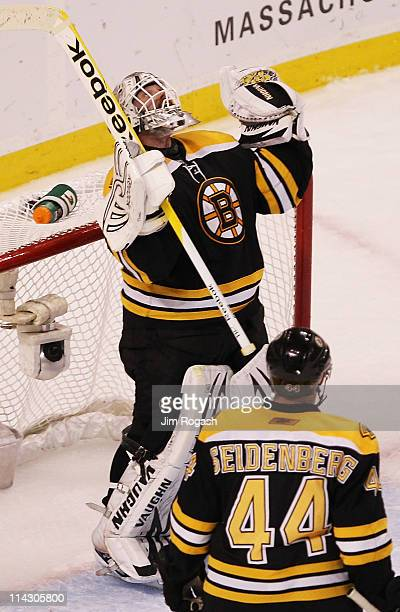 Tim Thomas of the Boston Bruins celebrates their 6 to 5 win over the Tampa Bay Lightning with teammate Dennis Seidenberg in Game Two of the Eastern...