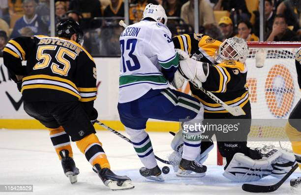 Tim Thomas of the Boston Bruins checks Henrik Sedin of the Vancouver Canucks during Game Three of the 2011 NHL Stanley Cup Final at TD Garden on June...