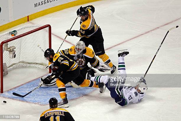 Tim Thomas of the Boston Bruins checks Henrik Sedin of the Vancouver Canucks as he tends goal during Game Three of the 2011 NHL Stanley Cup Final at...