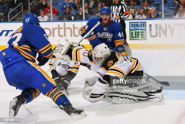 Tim Thomas of the Boston Bruins makes a save against Tyler Ennis and Andrej Sekera of the Buffalo Sabres at HSBC Arena on November 3 2010 in Buffalo...