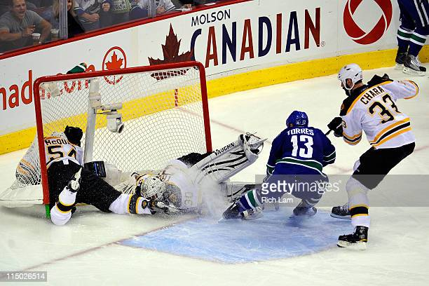 Tim Thomas of the Boston Bruins makes a save as Adam McQuaid smashes into the net during a play against the Vancouver Canucks in game one of the 2011...