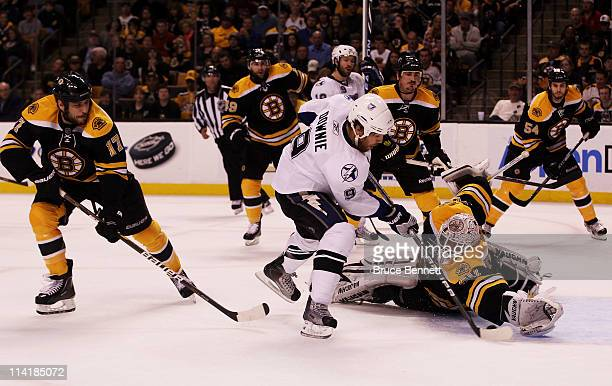 Tim Thomas of the Boston Bruins makes a second period save against Steve Downie of the Tampa Bay Lightning in Game One of the Eastern Conference...