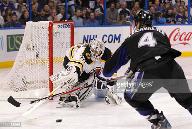 Tim Thomas of the Boston Bruins reaches to push the puck away from Vincent Lecavalier of the Tampa Bay Lightning during the third period in Game Four...