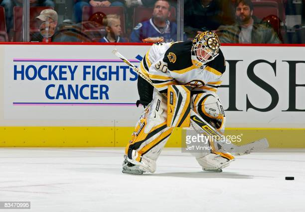 Tim Thomas of the Boston Bruins stands in front of a Hockey Fights Cancer sign as he watches his team during the warmup before their game against the...