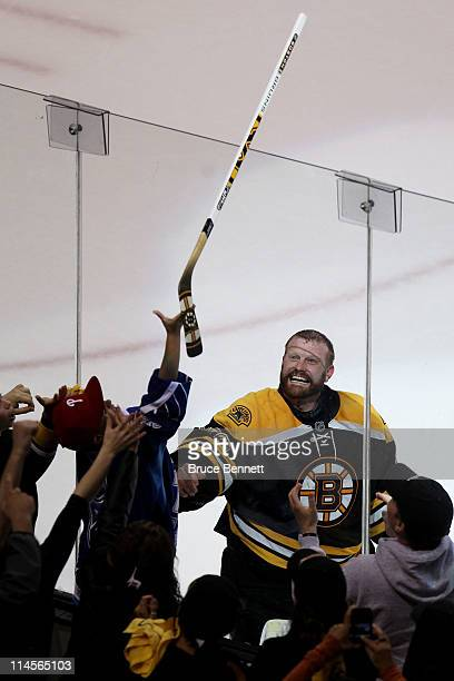 Tim Thomas of the Boston Bruins throws a stick to a fan after they defeated the Tampa Bay Lightning 3 to 1 in Game Five of the Eastern Conference...
