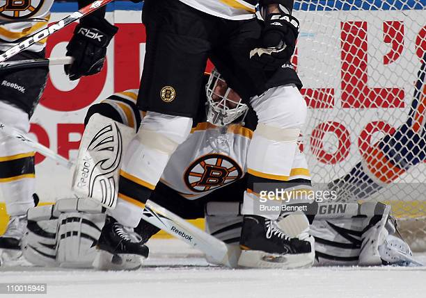 Tim Thomas of the Boston Bruins watches the action through the legs of Zdeno Chara in their game against the New York Islanders at the Nassau...