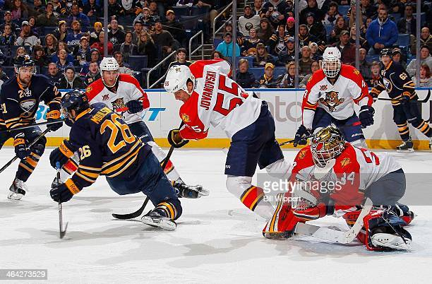 Tim Thomas of the Florida Panthers makes a third period save as Matt Moulson of the Buffalo Sabres is tripped by Ed Jovanovski of the Panthers on...