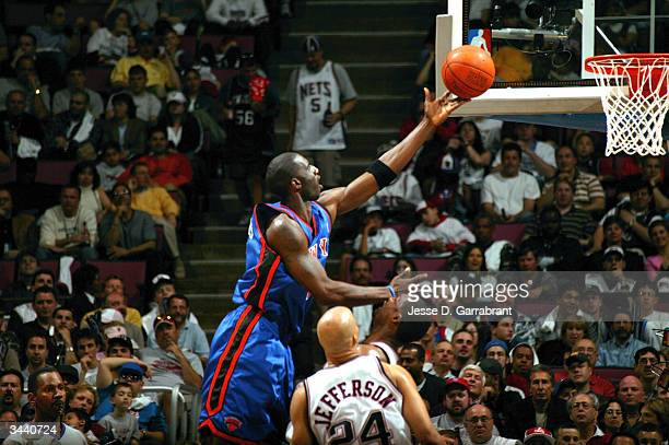 Tim Thomas of the New York Knicks attacks the basket against Rodney Rogers and Richard Jefferson of the New Jersey Nets during game one of round one...
