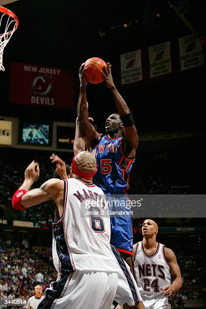 Tim Thomas of the New York Knicks goes strong to the basket against Kenyon Martin and Richard Jefferson of the New Jersey Nets on April 17 2004 at...