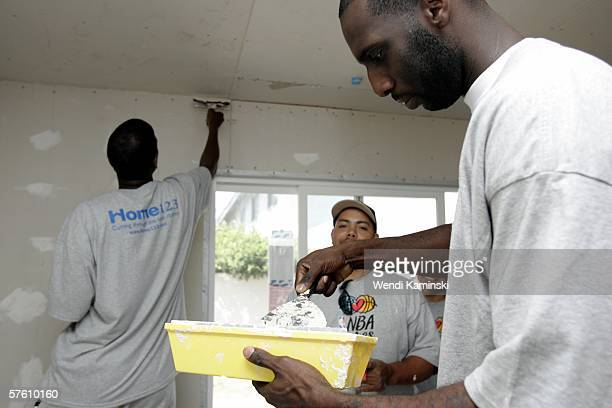 Tim Thomas of the Phoenix Suns helps spackle the living room of Maritza Jacobo's new home May 13 2006 in Torrance California NBA Cares and Home 123...