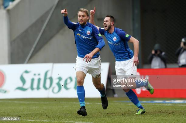 Tim Vaeyrynen of Rostock jubilates with team mate Pascal Breier after scoring the first goal during the 3Liga match between FC Hansa Rostock and SC...