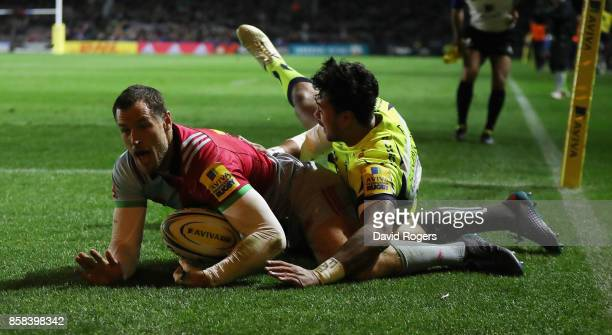 Tim Visser of Harlequins dives to score the first try despite being tackled by Denny Solomona during the Aviva Premiership match between Harlequins...