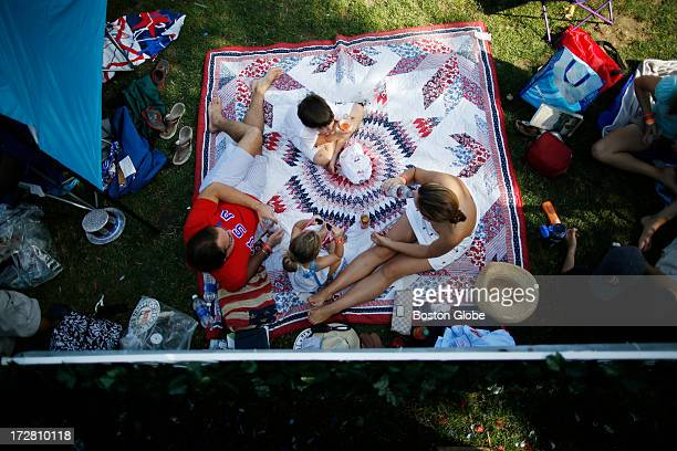 Tim Walker of Lafayette La left sits on a blanket with his son Bailey daughter Bliss and wife Sarah as they wait for the Boston Pops Fourth of July...