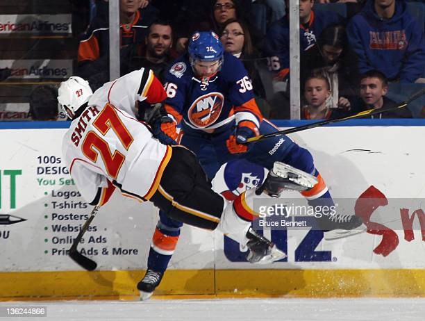 Tim Wallace of the New York Islanders checks Derek Smith of the Calgary Flames at the Nassau Veterans Memorial Coliseum on December 29, 2011 in...