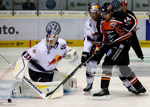 Tim Wallace of Wolfsburg and Daryl Boyle of Muenchen battle for the puck during the DEL match between Grizzly Adams Wolfsburg and EHC Red Bull...