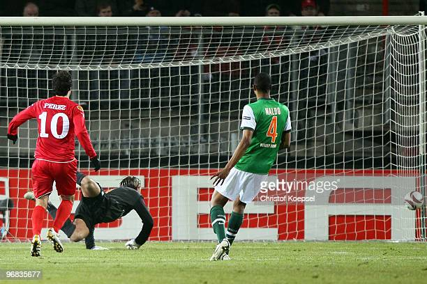 Tim Wiese of Bremen gets the first goal of Theo Janssen of Enschede during the UEFA Europa League knock-out round, first leg match between FC Twente...