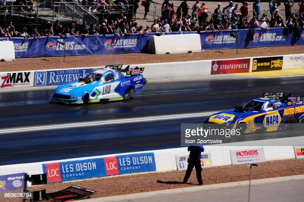 Tim Wilkerson Ford Shelby Cobra Mustang NHRA Funny Car burps some fire against Ron Capps Don Schumacher Racing Dodge Charger NHRA Funny Car in the...