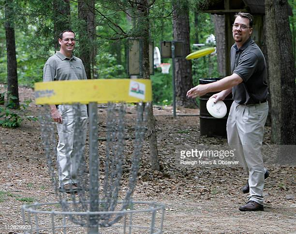 Tim Windsor left and Jeff Dennis take advantage of the nice weather to play a little disc golf during their lunch break at Cedar Hills Park in North...