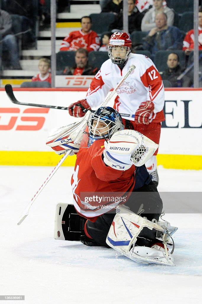 Tim Wolf #1 of Team Switzerland makes a glove save on the puck during the 2012 World Junior Hockey Championship game against Team Denmark at the Saddledome on January 2, 2012 in Calgary, Alberta, Canada.
