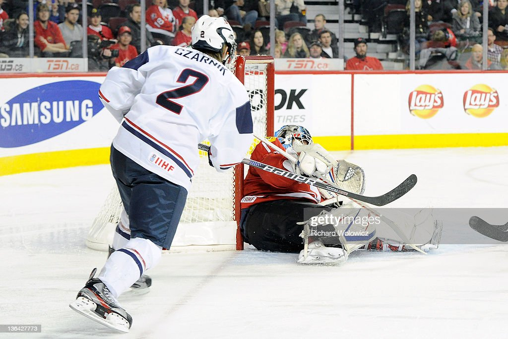 Tim Wolf #1 of Team Switzerland stops the puck on a shot by Austin Czarnik #2 of Team USA during the 2012 World Junior Hockey Championship Relegation game at the Scotiabank Saddledome on January 4, 2012 in Calgary, Alberta, Canada. Team USA defeated Team Switzerland 2-1.