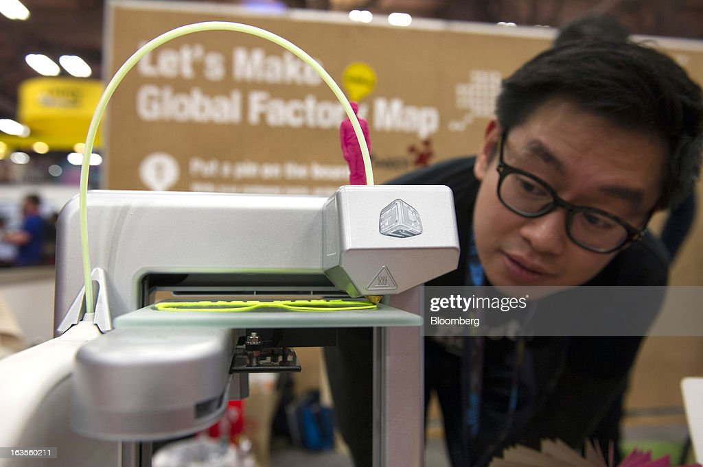Tim Wong, co-founder of FabCafe, watches his 3D printer make a pair of sunglasses at the South By Southwest Conference (SXSW) in Austin, Texas, U.S., on Monday, March 11, 2013. The 20th annual SXSW Interactive Festival takes place from March 8-12. Photographer: David Paul Morris/Bloomberg via Getty Images