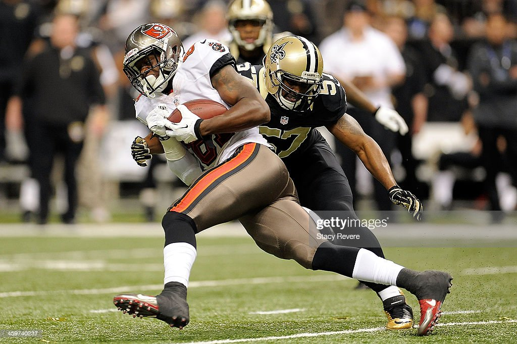 Tim Wright #81 of the Tampa Bay Buccaneers is brought down by David Hawthorne #57 of the New Orleans Saints during a game at the Mercedes-Benz Superdome on December 29, 2013 in New Orleans, Louisiana. New Orleans won the game 42-17.