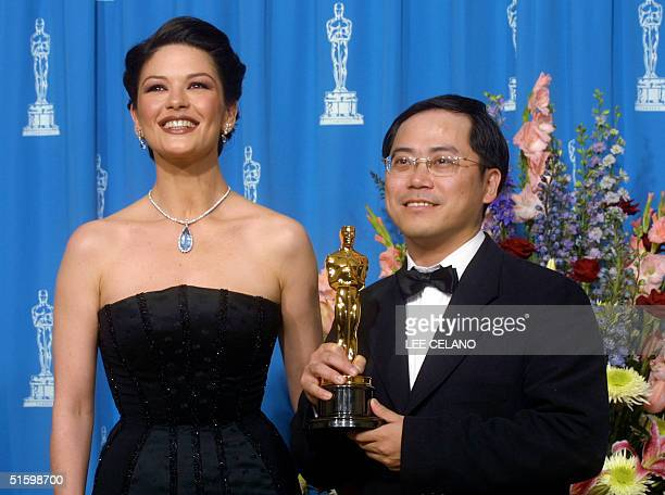 Tim Yip holds his Oscar for Best Art Direction for Crouching Tiger Hidden Dragon at the 73rd Annual Academy Awards at the Shrine Auditorium in Los...
