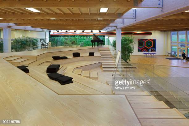 Timber amphitheatre on first floor with foliage covered green wall in background IBC Innovation Factory Kolding Denmark Architect schmidt hammer...