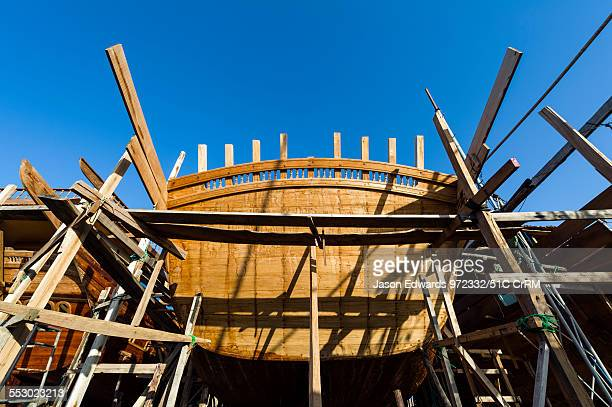 Timber and steel scaffolding supports the hull during handmade construction of an ancient timber dhow Sur Ash Sharqiyah Region Gulf of Oman Sultanate...