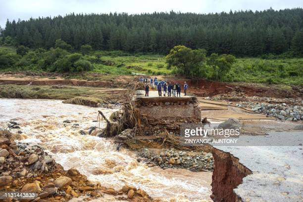 Timber company workers stand stranded on a damaged road on March 18 at Charter Estate, Chimanimani, eastern Zimbabwe, after the area was hit by the...