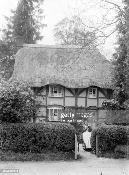 Timber framed cottage with a thatched roof, showing the owner standing by the gate with her cat, Uffington, Oxfordshire, c1916.