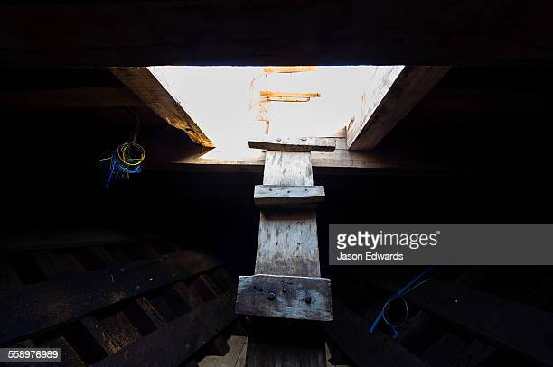 A timber ladder descends into the darkness of a dhow hull during construction.