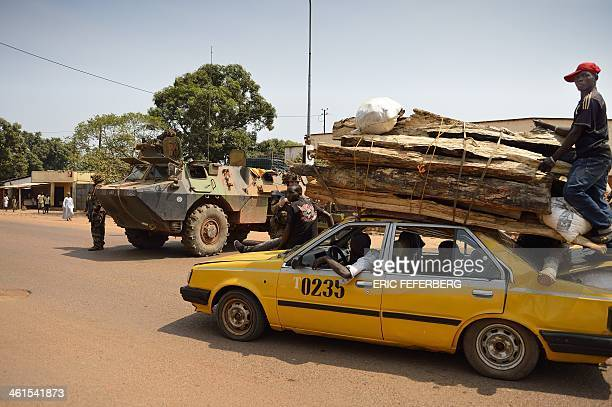 A timberladen taxi passes a French military armoured vehicle from the Sangaris forces watching the traffic looking for weapons on January 9 2014 in...